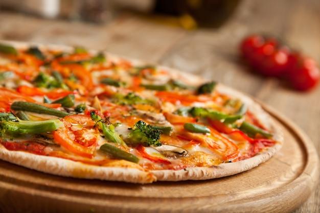木製のテーブルにイタリアンピザ「ベジタリアン」。ピザの上には、焼きたてのスライストマトとアスパラガスのブロッコリーがあります。近くにはスパイスとオリーブオイルの入った容器があります。それらの近くにチェリートマトがあります。