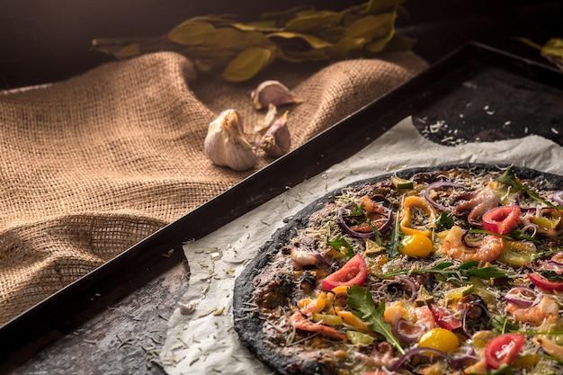 オーブンからのベーキングトレイに黒い生地とシーフードが入ったイタリアンピザ。その上にイカ、エビ、タコ、タマネギ、トマトを置きました。イカ墨