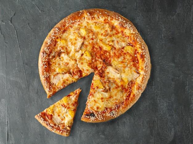 이탈리안 피자. 치킨, 파인애플, 토마토 소스, 모짜렐라 치즈, 설구니 치즈가 들어 있습니다. 넓은 쪽. 피자에서 한 조각이 잘립니다. 위에서 볼. 회색 콘크리트 배경에. 외딴.