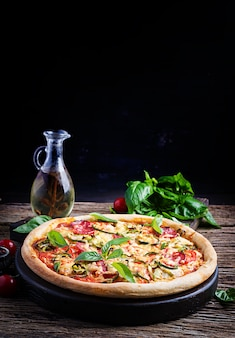 Italian pizza with chicken, salami, zucchini, tomatoes and herbs