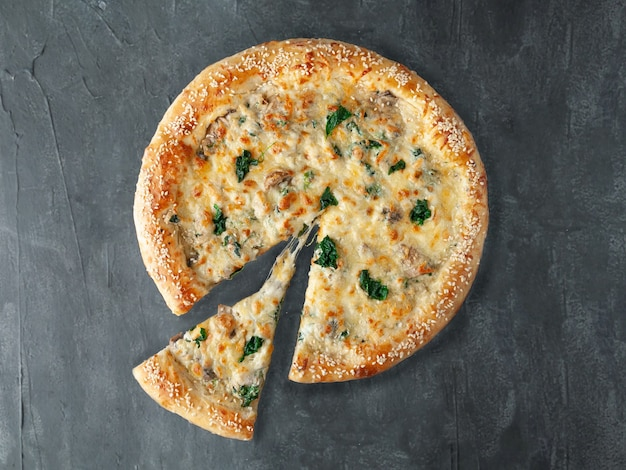 이탈리안 피자. 닭고기, 시금치, 버섯과 함께. 크림 소스에 모짜렐라 치즈와 설구니 치즈를 곁들인. 피자에서 한 조각이 잘립니다. 위에서 볼. 회색 콘크리트 배경에. 외딴.