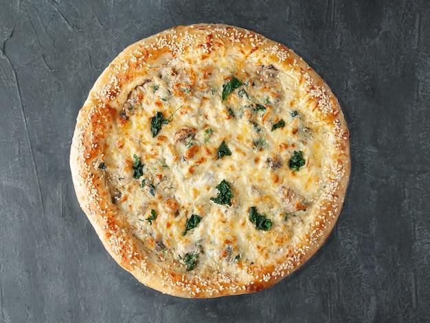 이탈리안 피자. 닭고기, 시금치, 버섯과 함께. 크림 소스에 모짜렐라 치즈와 설구니 치즈를 곁들인. 넓은 쪽. 위에서 볼. 회색 콘크리트 배경에. 외딴.