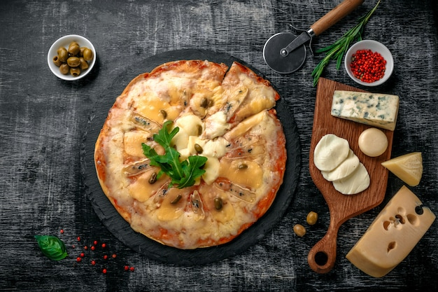Italian pizza with different sorts of cheese on a stone and a black scratched chalk board. italian traditional food