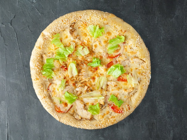 Italian pizza. with grilled chicken breast, tomatoes, lettuce, mozzarella and parmesan, caesar dressing. wide side. view from above. on a gray concrete background. isolated.