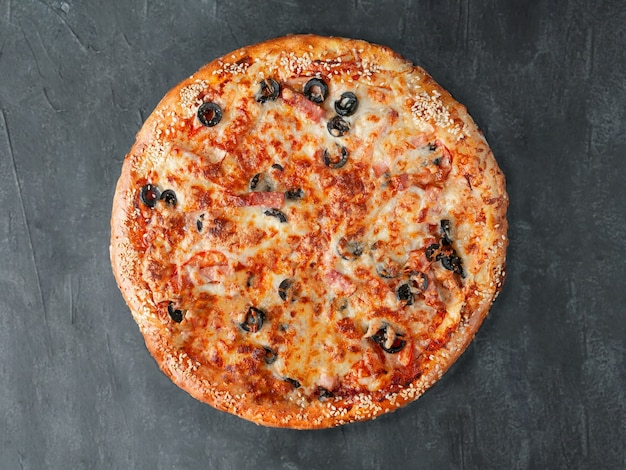 Italian pizza. with ham, cervelat, carbonate, bacon, tomatoes, olives, tomato sauce, mozzarella cheese. wide side. view from above. on a gray concrete background. isolated.
