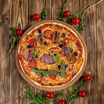ハム、トマト、オリーブ、バジルの木製のテーブルとイタリアのピザ。コピースペースの平面図