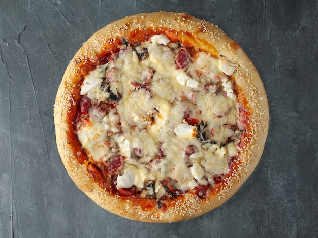 Italian pizza. with hunting sausages, feta cheese, red pepper, mushrooms, tomato, mozzarella cheese and tomato sauce. wide side. view from above. on a gray concrete background. isolated.