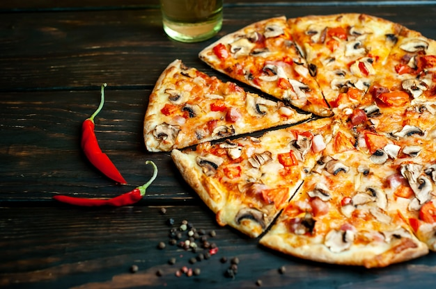 Italian pizza with mushrooms, tomatoes and cheese on wood