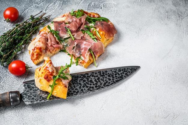 キッチンテーブルにパルマハム、ルッコラ、チーズを添えたイタリアンピザ