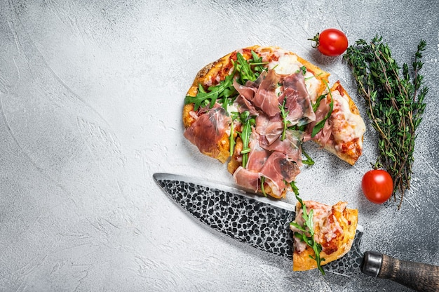 Italian pizza with  parma ham, arugula and cheeseon a kitchen table. white background. top view. copy space.