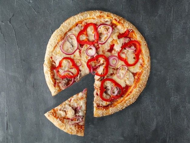 이탈리안 피자. 돼지고기, 소고기, 닭고기, 고추, 적양파, 토마토 소스, 모짜렐라 치즈가 함께 제공됩니다. 피자에서 한 조각이 잘립니다. 위에서 볼. 회색 콘크리트 배경에. 외딴.