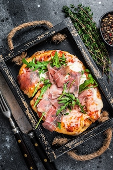 Italian pizza with prosciutto parma ham, arugula salad and cheese in a rustic wooden tray. black background. top view.