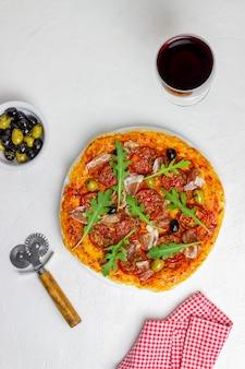 生ハム、トマト、ルッコラ、オリーブのイタリアンピザ。イタリア料理。レシピ。白色の背景。