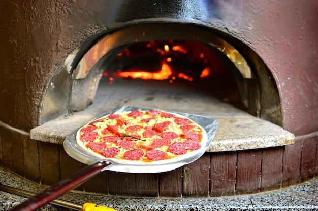 장작 오븐에 넣기 전에 살라미 소시지를 넣은 이탈리아 피자