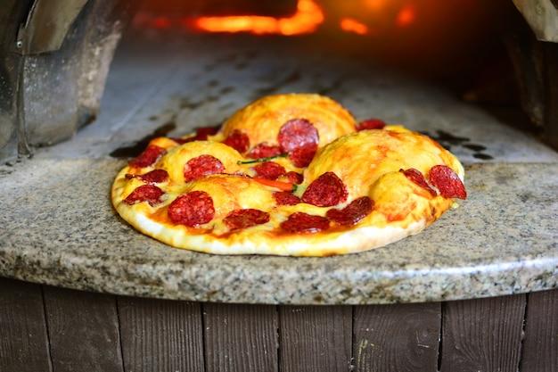 장작 오븐에서 구운 살라미를 곁들인 이탈리아 피자