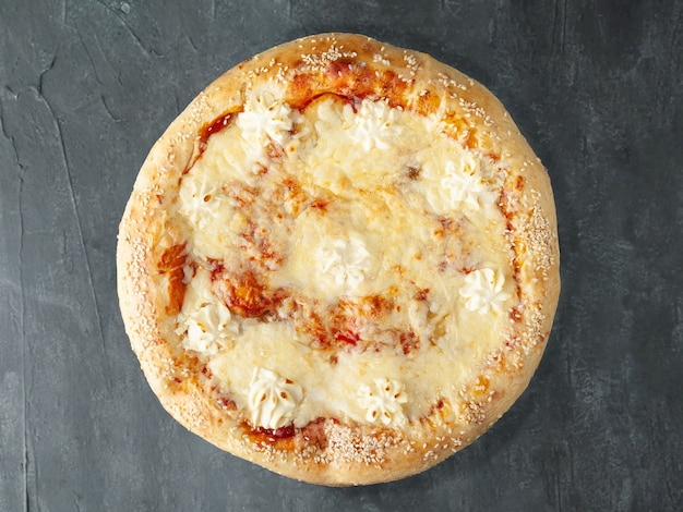 Italian pizza. with sweet pear, mozzarella, dutch cheese, philadelphia cheese, sulguni cheese, tomato sauce. wide side. view from above. on a gray concrete background. isolated.