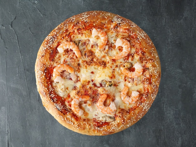 Italian pizza. with tiger prawns, squid, mussels, tomato sauce, mozzarella cheese. wide side. view from above. on a gray concrete background. isolated.