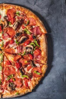 Итальянская пицца с помидорами, грибами, беконом, лососем и перцем. доставка еды на черном фоне