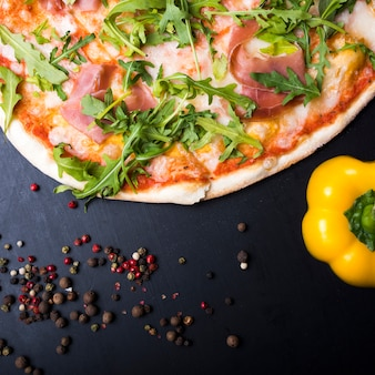 Italian pizza; yellow bell pepper and black pepper on kitchen counter