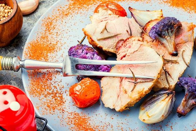 콜리플라워를 곁들인 이탈리아 돼지고기 포르체타입니다. 전통적인 이탈리아 축제 음식입니다.