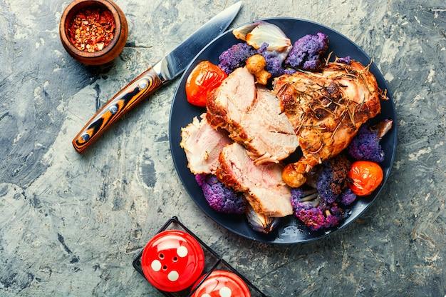 콜리플라워를 곁들인 이탈리아 돼지고기 포르체타입니다. 전통적인 이탈리아 휴일 음식입니다.