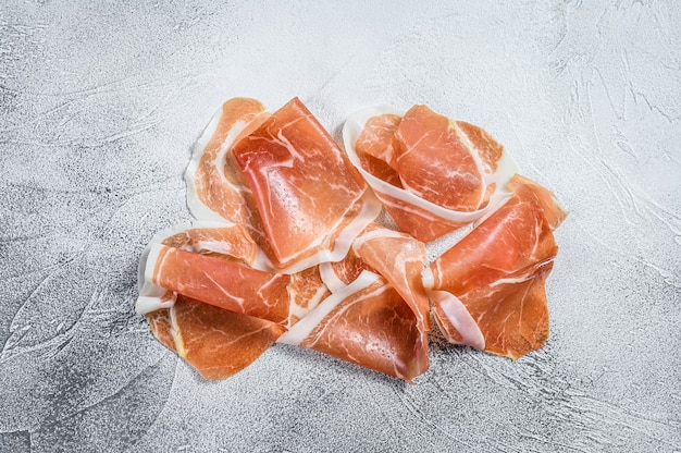 Italian prosciutto crudo, cured ham. white background. top view.