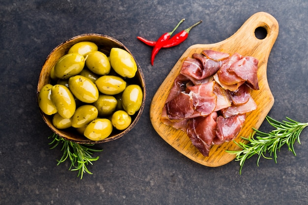 Italian prosciutto crudo or jamon with spice, olive, rosemary. flat lay