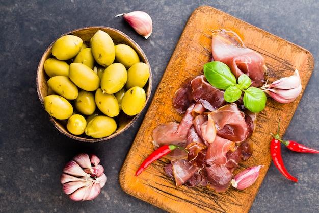 Italian prosciutto crudo or jamon with spice, olive, rosemary. raw ham.