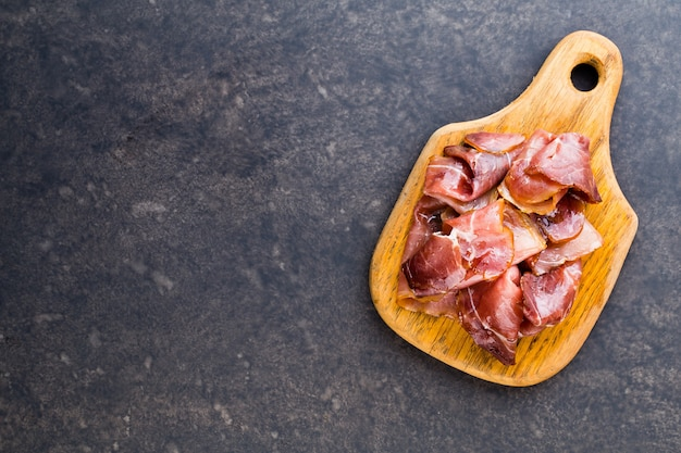 Italian prosciutto crudo or jamon with spice, olive, rosemary. raw ham.