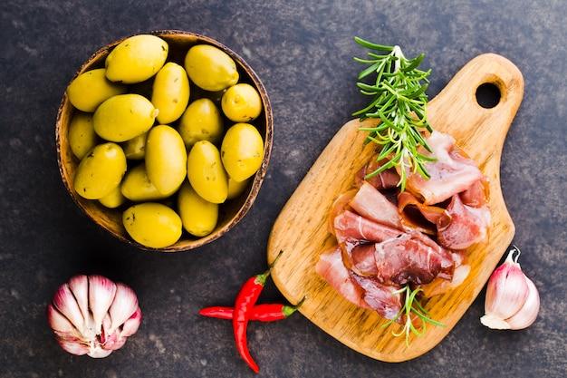 Итальянский прошутто крудо или хамон со специями, оливками, розмарином. сырая ветчина.