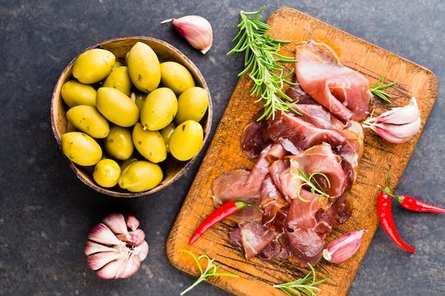 Итальянский прошутто крудо или хамон со специями, оливками, розмарином.
