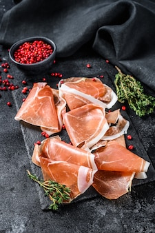 Italian prosciutto crudo with thyme, cured ham. black background. top view.