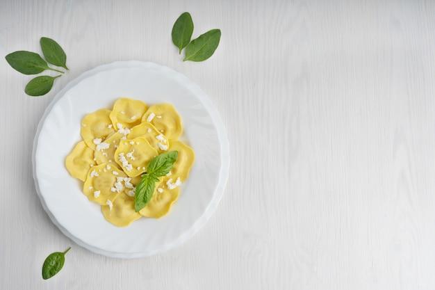 バジルの葉で飾られたパルメザンチーズを詰めたイタリアンラビオリパスタ。上面図