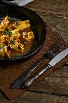검은 접시에 고기 근접 촬영으로 박제 이탈리아 라비올리. 소박한 스타일.