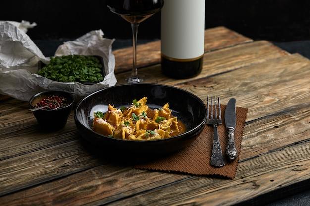 Итальянские равиоли, фаршированные мясом крупным планом на черной тарелке. деревенский стиль.