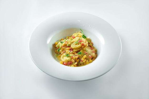 白いプレートの白いプレートに野菜のサルサとパルメザンチーズを添えたさまざまなフィリング(肉、チーズ)のイタリアンラビオリ
