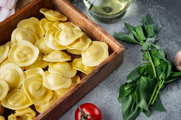 신선한 재료, 바질, 페스토, 햄, 모짜렐라 치즈, 파마산 세트, 나무 상자에, 회색 테이블에 이탈리아 생 수제 라비올리