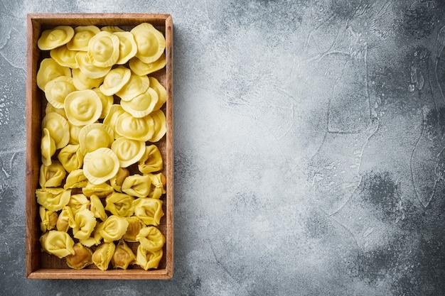 이탈리아 원시 수제 tortellini 및 ravioli 세트, 나무 상자, 회색 테이블, 평면도 평면 배치