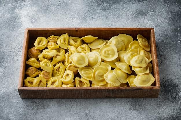 회색 테이블에 나무 상자에 이탈리아 원시 수제 tortellini 및 ravioli 세트