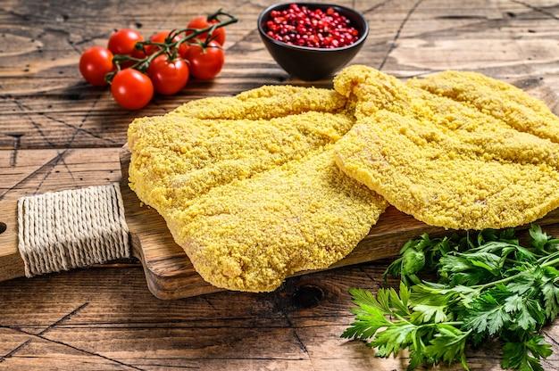 Итальянский сырой миланский шницель. деревянный фон. вид сверху.