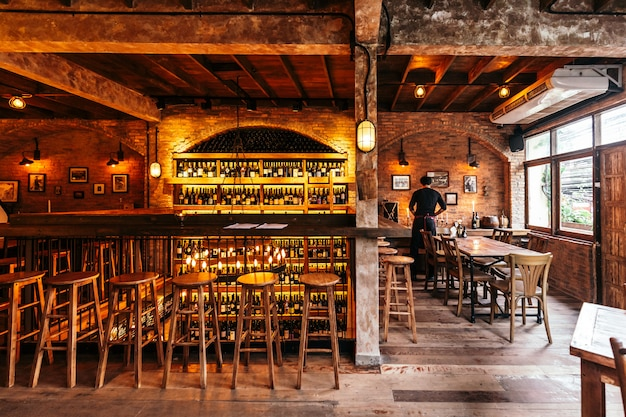 Italian restaurant decorated with brick in warm light that created cozy atmosphere with waiter on the right table. counter table with wine cellar on the wall.