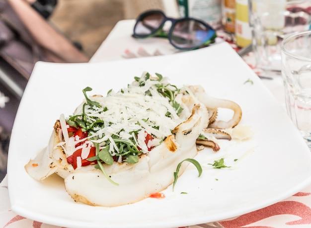 プーリア地方(南イタリア)のガリポリにあるイタリアンレストラン。新鮮なサラダ、トマト、本物のパルミジャーノチーズを添えた伝統的なイカ。明け。