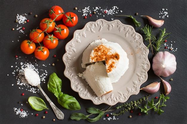 Итальянский сыр рикотта, овощи и зелень на темном столе