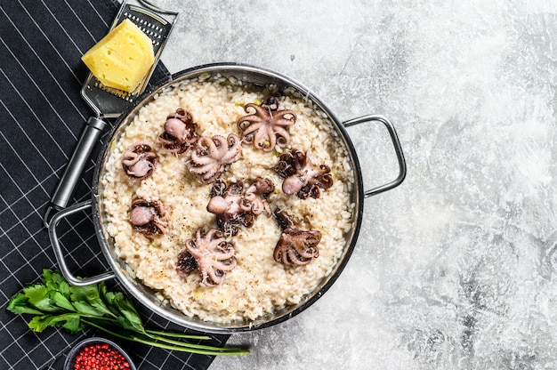 Italian risotto with octopus and mushrooms. gray background. top view. space for text