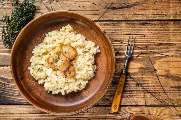 Итальянский ризотто с морскими гребешками на сковороде. деревянный фон. вид сверху. скопируйте пространство.