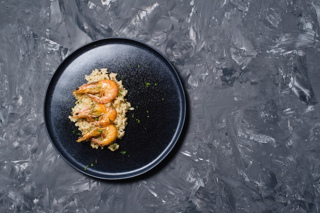 Italian risotto with shrimp on a black plate.