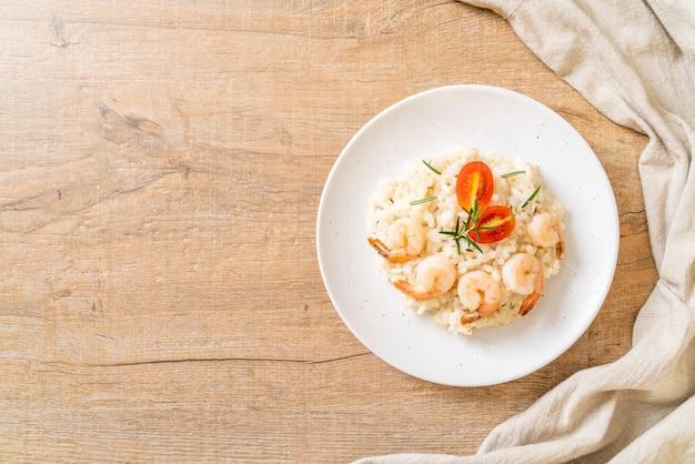 Итальянское ризотто с креветками на белой тарелке