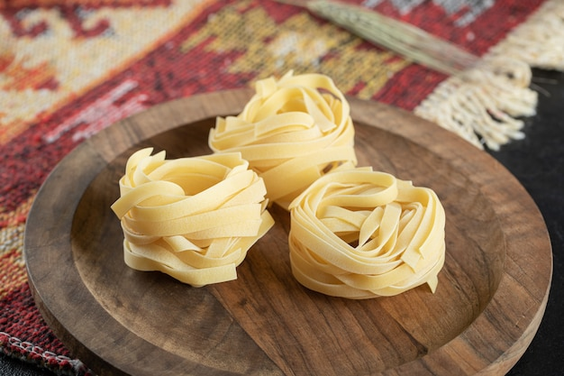 Italian rolled uncooked fettuccine pasta on wooden board with wheat