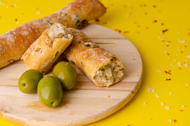 Italian rustic olive bread sticks on yellow background with copy space