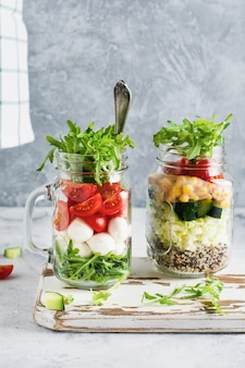 Italian salad of arugula, mozzarella and cherry tomato served in a jar for lunch on the table